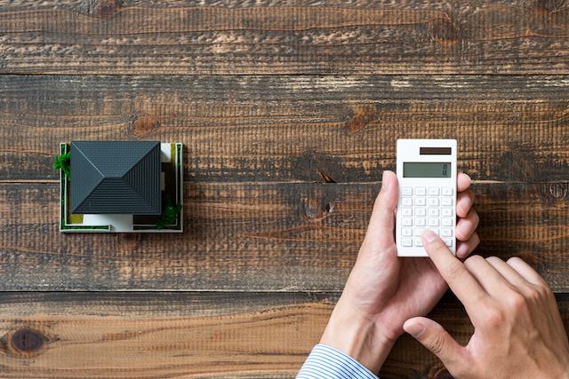 Mann mit Taschenrechner ermittelt den richtigen Immobilienpreis für sein Haus