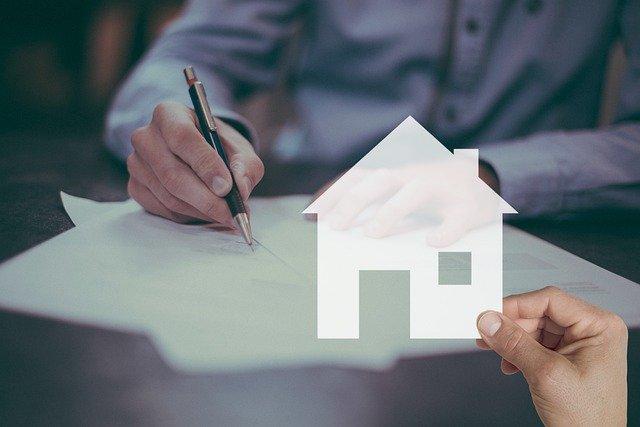 Mann unterschreibt Notarvertrag für Immobilienverkauf